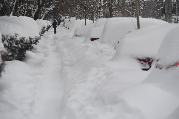 Un hombre camina junto a los automóviles cubiertos de nieve en Bucarest, Rumania. (AFP).