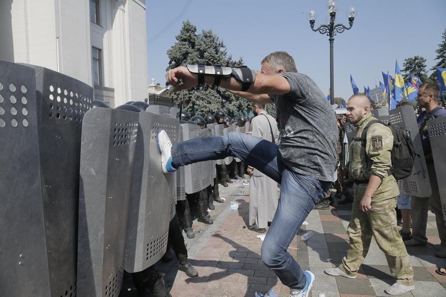 Un inconforme agrede a los policías durante las manifetaciones ocurridas este lunes en Kiev. (Foto Prensa Libre: AP).
