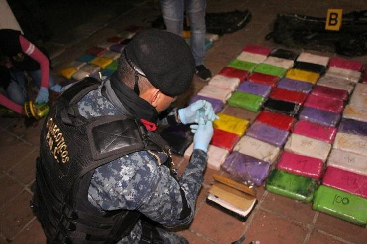 Autoridades durante el conteo de la droga incautada en buque que atracó en Puerto Quetzal. (Foto Prensa Libre: PNC)