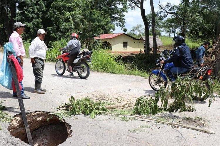 Algunos vecinos colocaron ramas y piedras en los alrededore de los agujeros para evitar accidentes. (Foto Prensa Libre: Rigoberto Escobar)