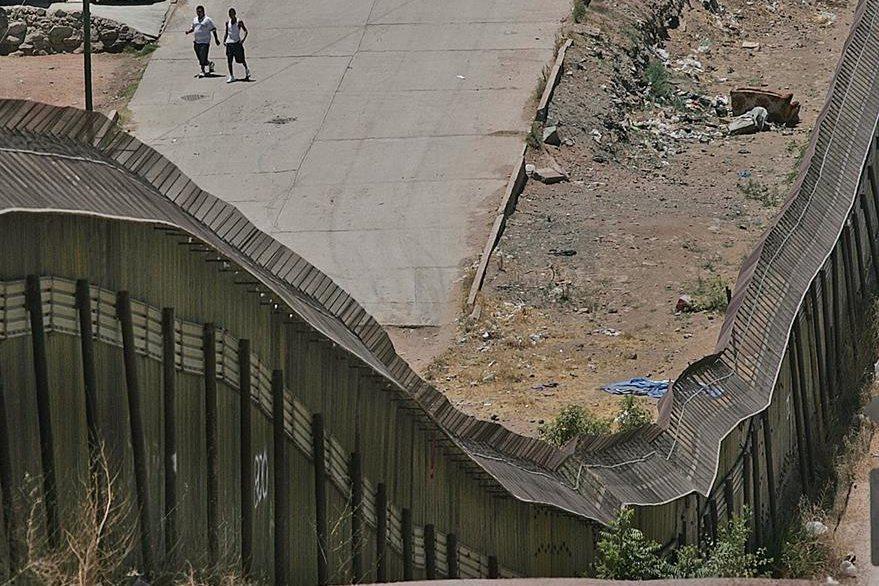 Dos hombres caminan en Nogales, México, al lado izquierdo el muro visto desde Nogales, Arizona.(AP).