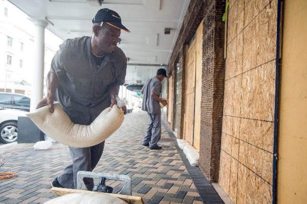 """Trabajadores protegen un comercio ante la llegada de """"Joaquín"""" an Bahamas."""