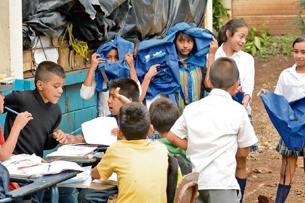 Estudiantes de  la escuela de la aldea El Pino, Barberena, muestran mochilas rotas. (Foto Prensa Libre: Oswaldo Cardona)