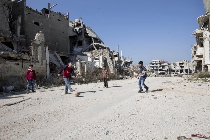 Niños sirios juegan futbol en medio de las ruinas de Homs. (Foto Prensa Libre: AP).