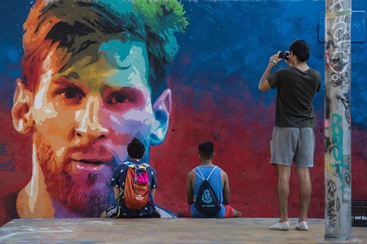 El presidente del Real Madrid, Florentino Pérez aseguró que le hubiera gustado tener en su equipo a Leo Messi. Dos jovenes observan un mural con el rostro de Messi. (Foto Prensa Libre: AFP)