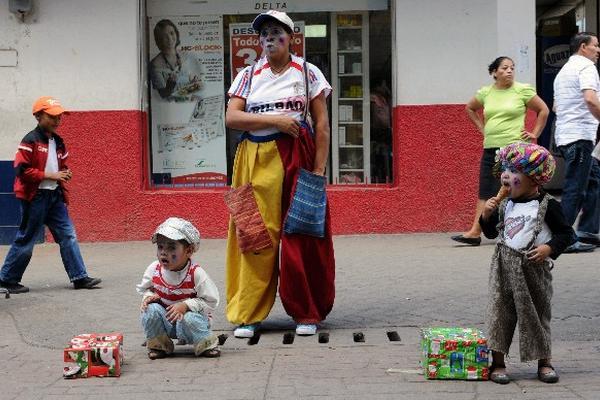 Una Mujer y sus hijos se visten como  payasos para ganar dinero  en Tegucigalpa, Honduras.
