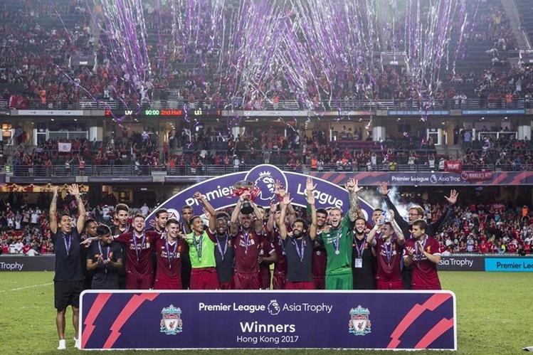 Los jugadores del Liverpool posan con el trofeo luego de conquistar el torneo Premier Asia. (Foto Prensa Libre: AFP)