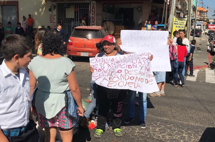 Portando carteles, padres de familia exigen la destitución de la junta escolar. (Foto: Cortesía)