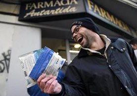 Un hombre sale de una farmacia en Montevideo, Uruguay, tras haber adquirido marihuana en dos presentaciones. (Foto Prensa Libre: AP)