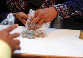 Una mujer intercambia monedas en Allahabad, India.(Foto Prensa Libre: AFP).