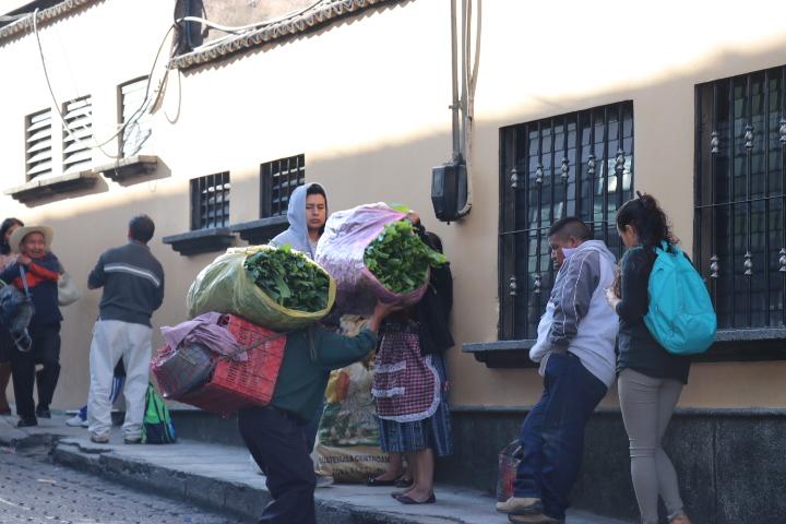 Un hombre carga su mercadería ante la disminución del servicio de buses. (Foto Prensa Libre: Héctor Cordero)