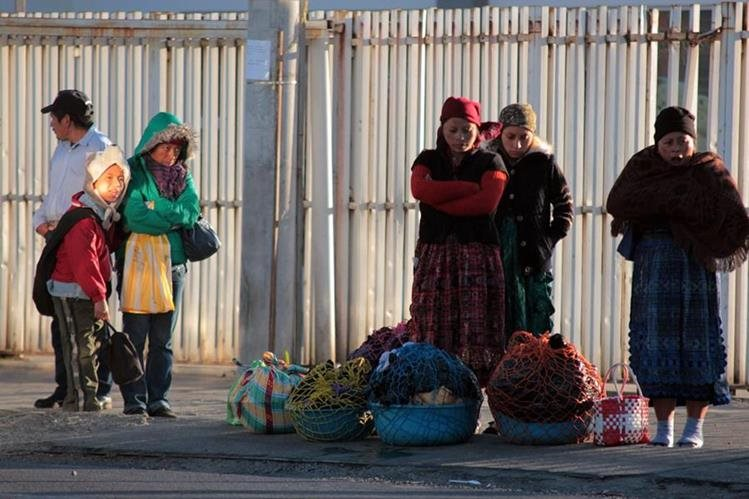 Bien abrigados, usuarios del transporte urbano en Quetzaltenango, esperan el bus en una estación. (Foto Prensa Libre: Carlos Ventura)
