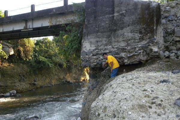 vecino señala la base  del puente    que está  dañada  debido  a la  crecida   del río Siguacán, en la aldea Día de Reyes, Santa Bárbara, Suchitepéquez.