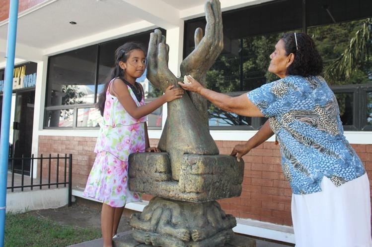 Ashly Ríos –izq- y Evangelina Gutiérrez colocan una rosa en el monumento a la Paz, en Jutiapa. (Foto Prensa Libre: Óscar Figueroa).