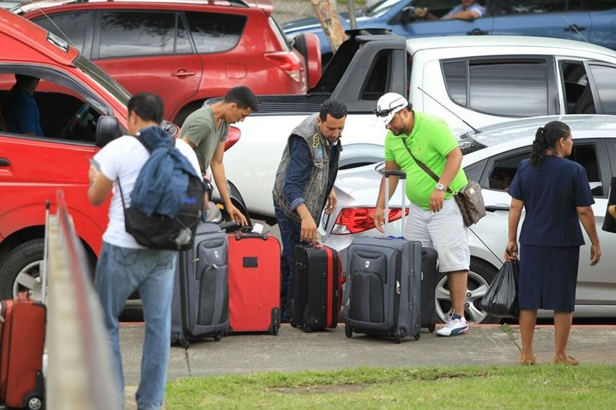 Decenas de viajeros deben cargar con sus maletas a pie porque la protesta bloquea el acceso a vehículos al aeropuerto. (Foto Prensa Libre: Esbin García)