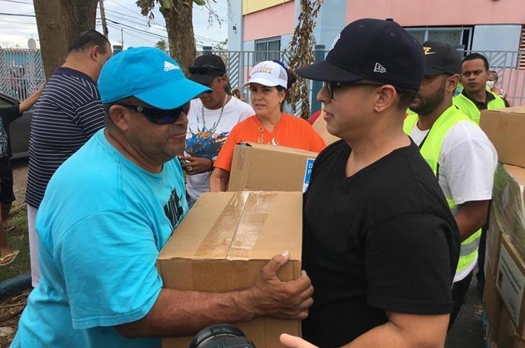 El cantante urbano Daddy Yankee (d) e integrantes del Banco de Alimentos de Puerto Rico entregan cajas de comida a ciudadanos afectados por el huracán María (Foto Prensa Libre: EFE).