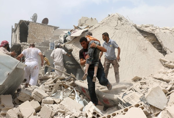 Un sirio lleva a un niño herido por el ataque con bomba barril en Bab al-Nairab de Alepo.(AFP).