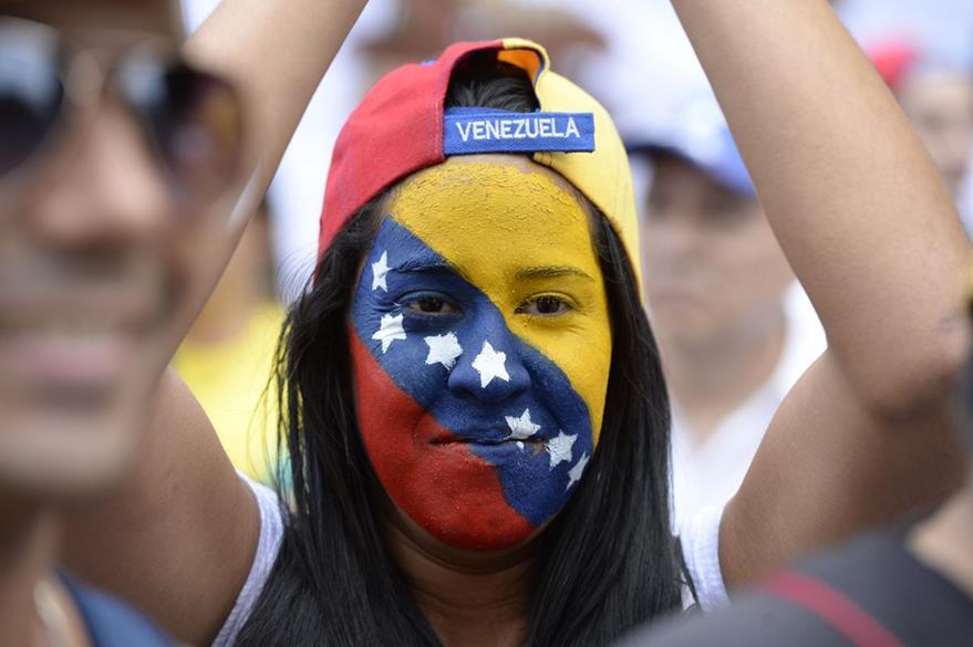 Una mujer con los colores de la bandera venezolana también marcha en las calles de Caracas. (Foto Prensa Libre: AFP).