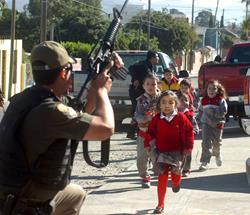 Fotografía cedida del 2008 que muestra a policías federales mexicanos poniendo a salvo a un grupo de niños, durante un tiroteo en el que participaron agentes federales y soldados contra sicarios en la ciudad mexicana de Tijuana. (Foto Prensa Libre: EFE)