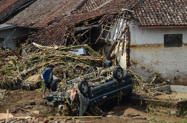 Un hombre inspecciona un vehículo dañado por la inundación en Garut, Java, Indonesia. (AP).