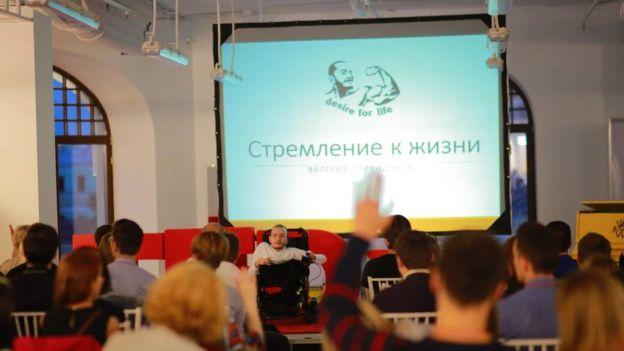 El ruso dando una charla sobre la organización Desire for Life, cuyo logo es su cara exhibiendo un musculoso brazo. DESIRE FOR LIFE