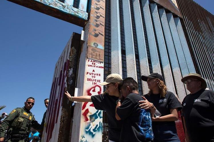 Familias se despiden de sus seres queridos, después de haberse abrazado, en la frontera entre Tijuana, México, y San Diego, EE. UU. (Foto Prensa Libre: AFP)