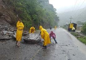 Trabajadores retiran derrumbe causado por la lluvia en Huehuetenango este martes. (Foto Prensa Libre: Conred).
