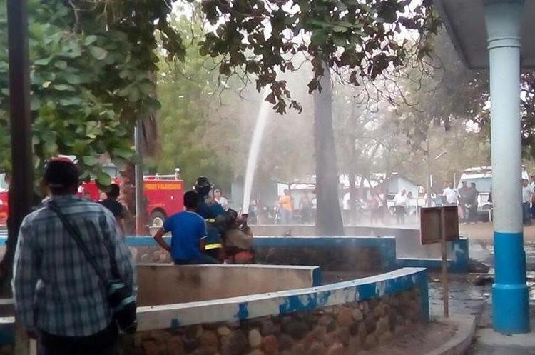 Bomberos apagan el fuego que causó la descarga. (Foto Prensa Libre: Mario Morales)