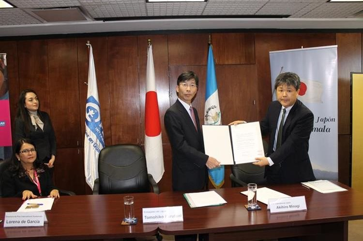 El embajador del Japón Tomohiko Furutani y el representante del Plan Internacional Akihiro Minagi muestran el convenio suscrito. (Foto Prensa Libre: Antonio Jiménez)