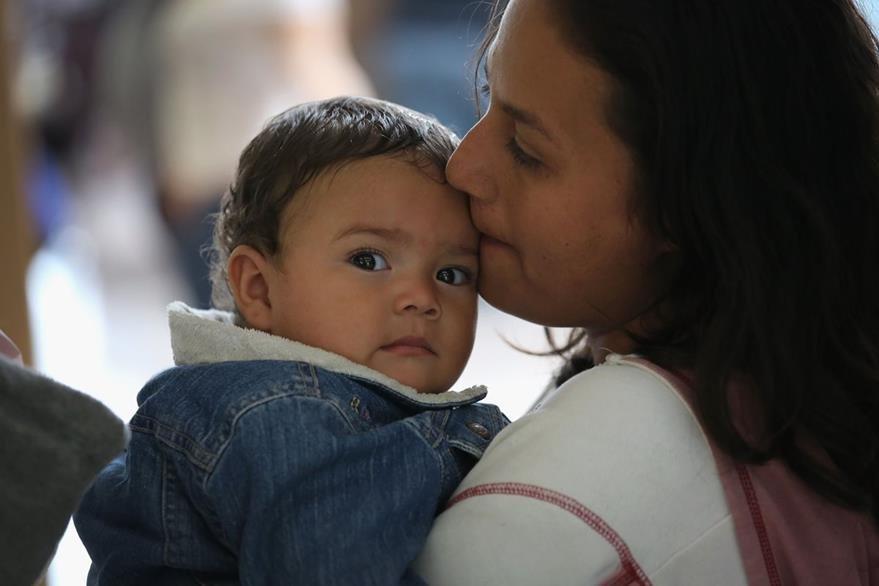 Un amadre, migrante hondureña y su hija en un centro de control migratorio en Mcallen, Texas. (Foto Prensa Libre: AFP).