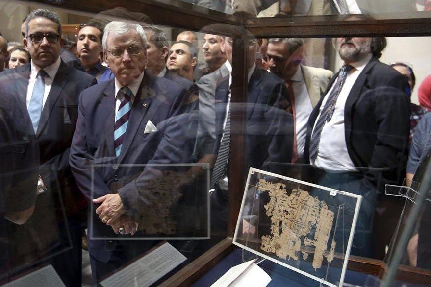 El ministro egipcio de Antigüedades, Khaled al-Enany (i), posa junto al papiro del rey Yufu. (Foto Prensa Libre: EFE).
