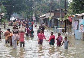 Una pareja busca sus pertenencias tras las inundaciones en el distrito de Morigaon, en Assam India.(Foto Prensa Libre: EFE)
