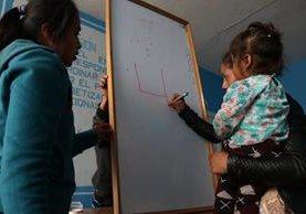 Una mujer con su hija en brazos escribe en una pizarra en Huehuetenango. (Foto Prensa Libre: Mike Castillo)