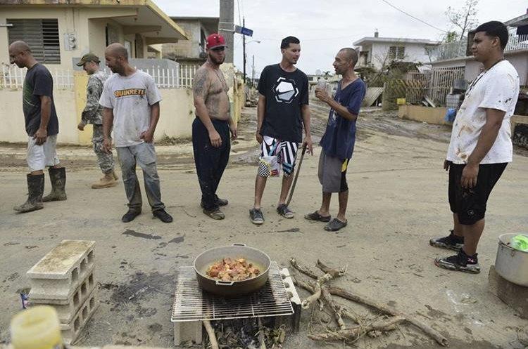 Residentes de Toa Ville cocinan en la calle después del paso del huracán María, en Toa Baja, Puerto Rico. (Foto Prensa Libre: AP)