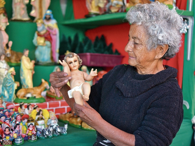 """María Herlinda Campos  tiene 70 años de vender imaginería para nacimientos. """"Desde los 10 años vengo  a vender. Ya tengo clientes que me buscan... Es una tradición familiar que ya lleva tres generaciones"""", cuenta mientras uno de sus nietos atiende a los clientes. """"Aunque ya no se vende igual, siempre venimos"""", dice."""