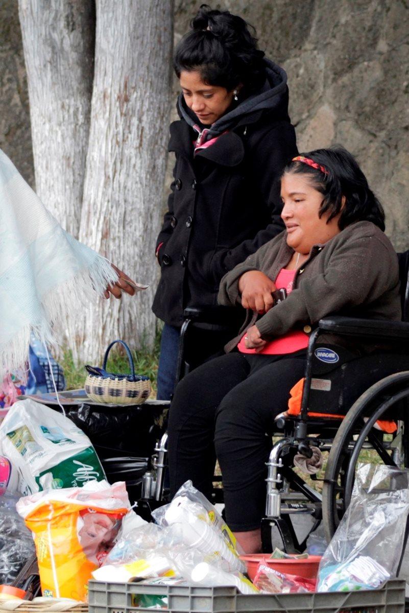 Vecinos de Xela compran productos a Ruth López, quien los ofrece afuera del HRO. (Foto Prensa Libre: María José Longo)