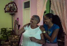 Yolanda Mollinedo mira a su nieta Alejandra en Virginia, EE. UU., en su smartphone usando una app de videochat junto a su sobrina Yulisleidi, con nuevo servicio experimental de internet en su casa en La Habana, Cuba. (Foto Prensa Libre: AP).