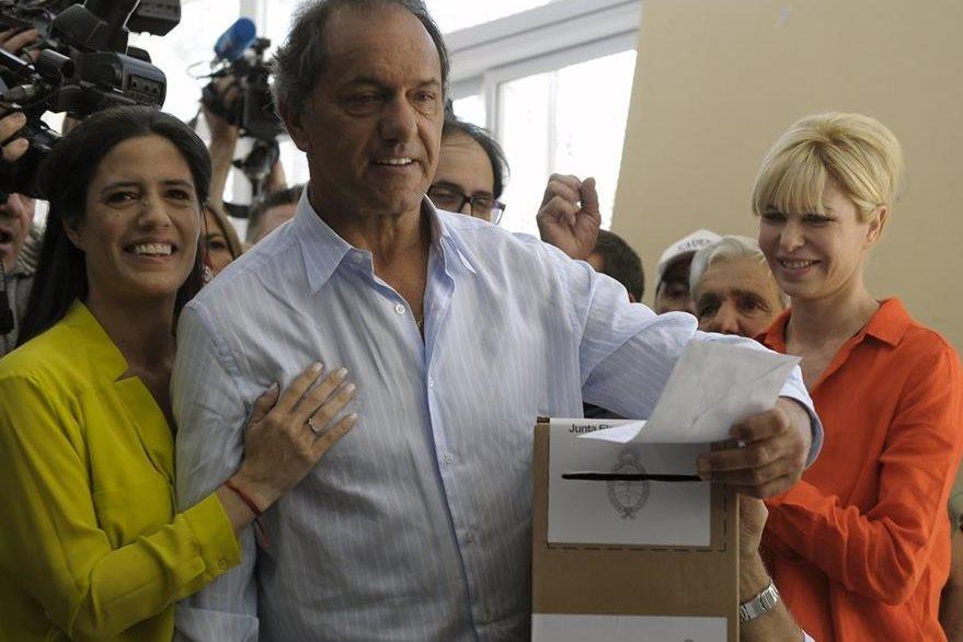 El candidato oficialista Daniel Scioli vota junto con su esposa, Karina Rabolini, y su hija, Lorena. (AFP)