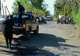 Agentes de  la PNC trasladan cadáver calcinado de un hombre en Puerto San José, Escuintla. (Foto Prensa Libre: Carlos Enrique Paredes)