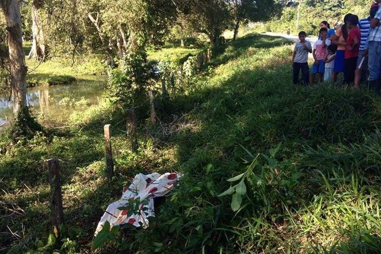 Vecinos y curiosos observan el cuerpo sin vida de Calos Yovani Revolorio, de 19 años, quien se presume murió ahogado en un río en Dolores, Petén. (Foto Prensa Libre: Walfredo Obando)