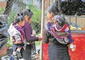 Niñas madres de San Juan Atitán, Huehuetenango, captadas en la plaza del municipio, mientras cargan a sus hijos.