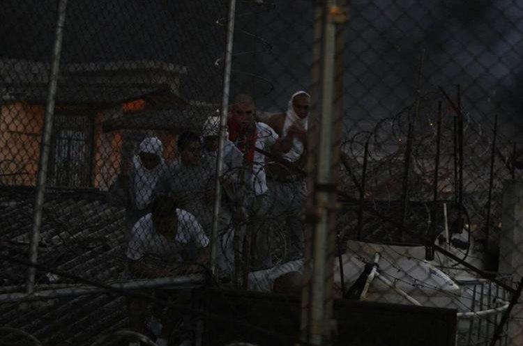 Internos caminan por el techo. Al fondo, un incendio.  (Foto Prensa Libre: Paulo Raquec)