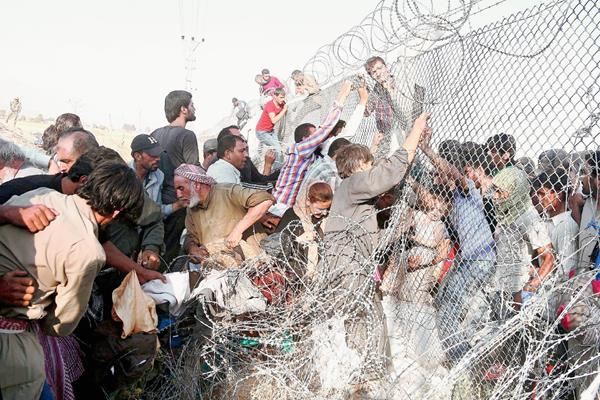 Sirios que huyen de la guerra en su país derriban la malla fronteriza con Turquía a donde ingresaron para resguardar sus vidas. Hombres mujeres y niños buscan refugio en el vecino país. (Foto Prensa Libre: EFE).
