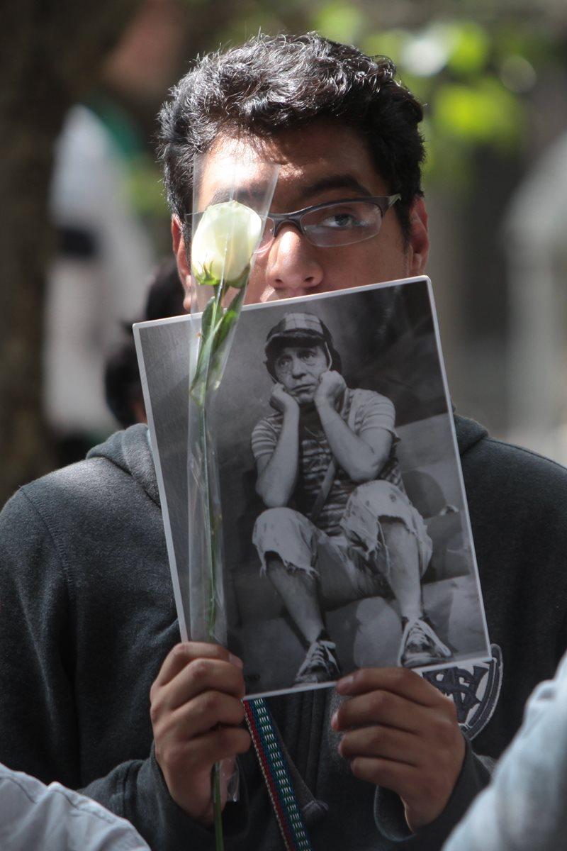 Un joven muestra una fotografía del Chavo del Ocho durante una misa por el primer aniversario de la muerte del comediante mexicano. (Prensa Libre: EFE)