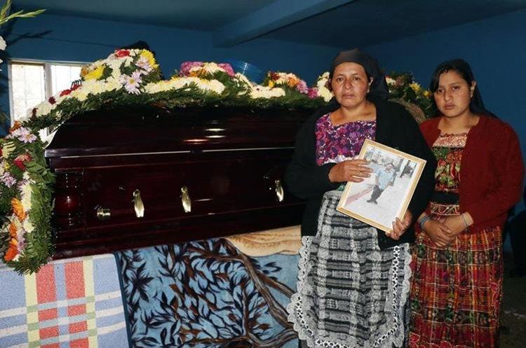 Familiares muestran una fotografía de la víctima
