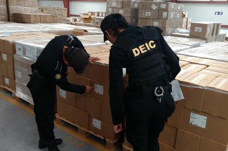 Agentes de la DEIC verifican fecha de vencimiento de medicamentos en bodegas del Ministerio de Salud. (Foto Prensa Libre: PNC).