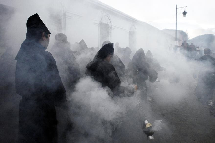 Penitentes esparcen incienso mientras se aproxima la urna con los restos simbólicos de Jesús durante la procesión del Santo Entierro. Foto: EFE/Ulises Rodríguez