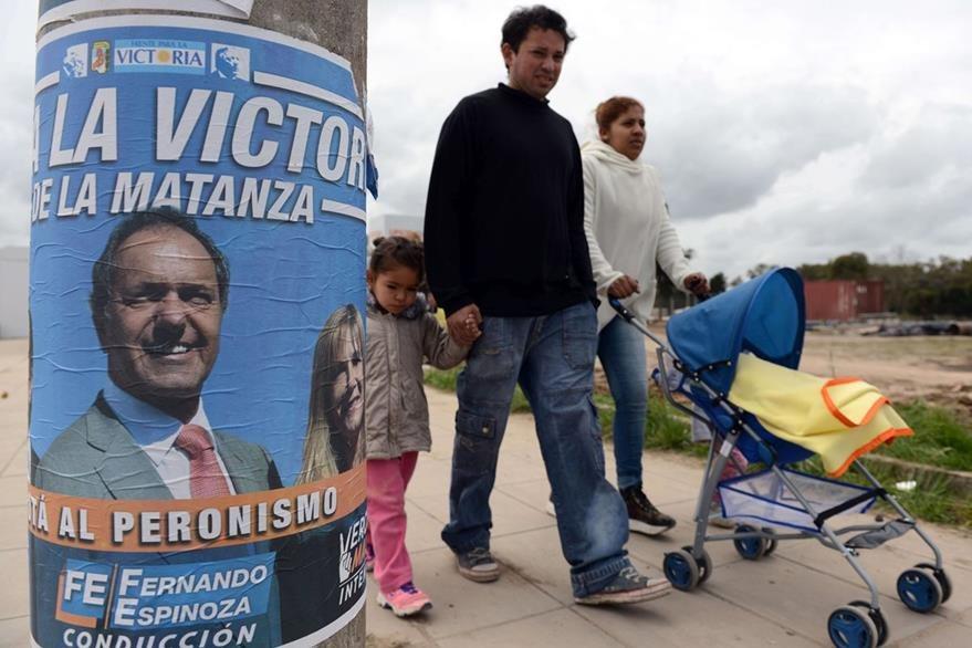 Una familia camina en una calle de Buenos Aires, en un poste figura la propaganda del candidato oficialista. (Foto Prensa Libre: AFP).