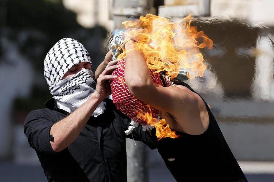 Un palestino intenta ayudar a un compañero que se ha prendido fuego al lanzar un cóctel molotov contra soldados israelíes. (Foto Prensa Libre: EFE).