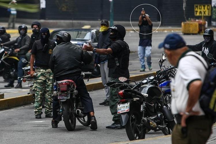 Un grupo de supuestos civiles encapuchados impiden el paso de manifestación en Caracas. (Foto Prensa Libre: EFE)